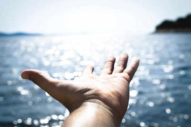 自由 手 輝く海面